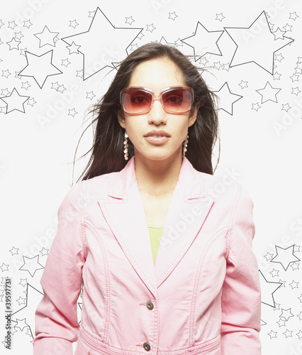 Woman posing for the camera in sunglasses against man made background