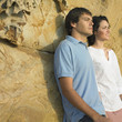 Young couple leaning against rock