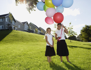 Portrait of two girls holding balloons in backyard
