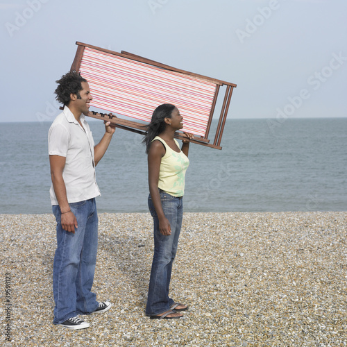 Young couple posing with folded lounge chair on beach