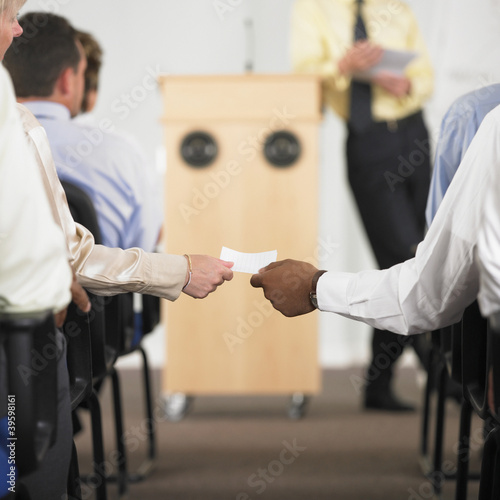 Hands exchanging note in business conference
