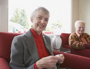 Senior woman knitting with husband watching