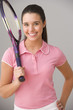 Portrait of teenage girl smiling and holding tennis racket