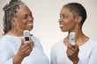 Mother and daughter looking at each other while holding cell phones