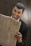 Portrait of businessman reading newspaper