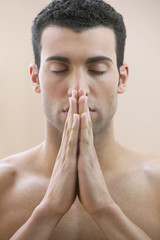 Man praying with hands in front of face