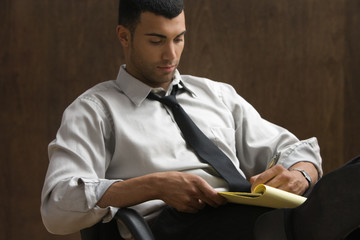 Businessman sitting and writing notes