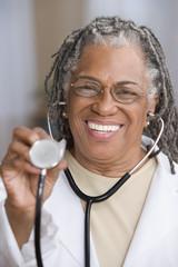 Portrait of female doctor holding stethoscope up