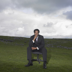 Businessman sitting in a rural meadow