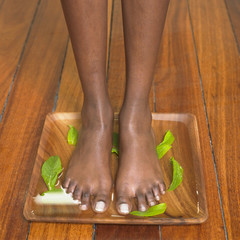 Young woman standing on a wooden tray of water