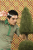 Young man trimming a shrub with hand scissors