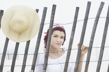 Young woman smiling for the camera behind a makeshift fence