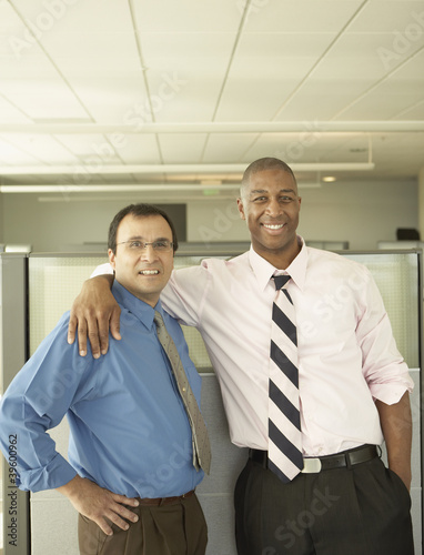 Businessmen smiling for the camera in empty office space