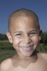 Young boy smiling for the camera with wet hair