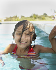 Young girl smiling for the camera in a swimming pool
