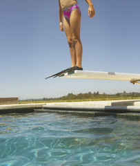 Man in flippers standing on a diving board
