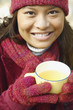 Young woman having a cup of tea outdoors
