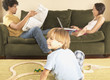 Parents on sofa and young son playing with trains on floor