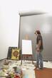 Male artist considering a blank easel