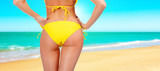 Closeup of a female backside in a yellow swimsuit