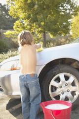 Young boy washing car