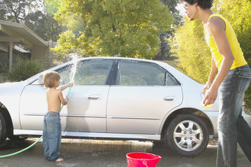 Father and young son washing car