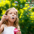 Cute girl blowing bubbles oudoors.