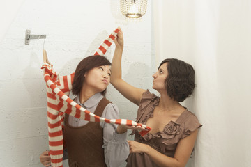 Young woman trying on a sweater in fitting rooms