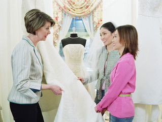 Tailor helping young women pick bridal fabric