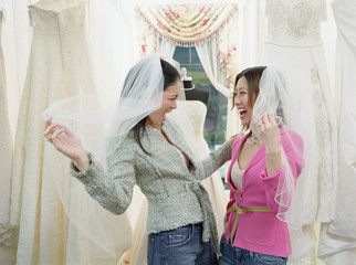 Young women wearing veils in a bridal boutique