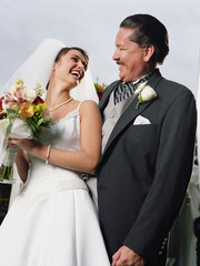 Bride posing for the camera with her father