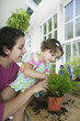 Mother and her daughter gardening in a greenhouse