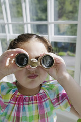 Young girl looking through binoculars in a greenhouse