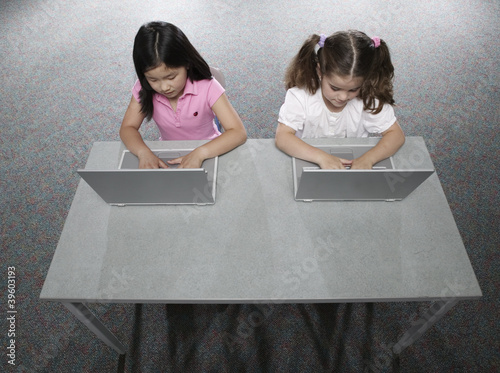 Two girls in classroom with laptops