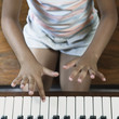 Midsection of girl playing piano