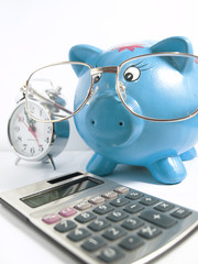 Bussines concept-Piggy bank with glasses,calculator and a clock