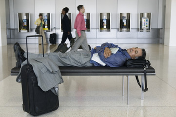 Businessman sleeping at airport