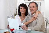 Mature couple using a credit card online