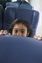 Portrait of young girl peeking over airplane seat