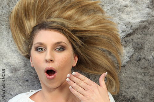 Woman lying open mouthed on a plush carpet