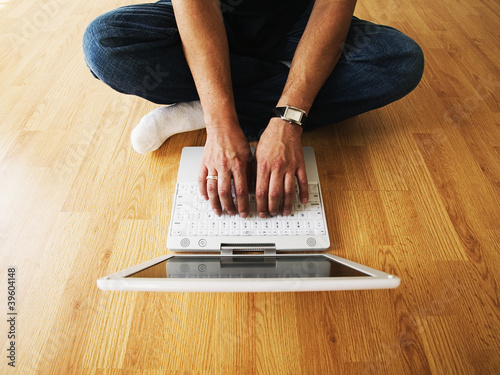 Low section of man typing on laptop