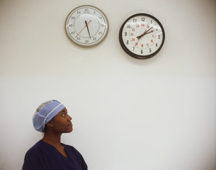 Female surgeon looking at clocks