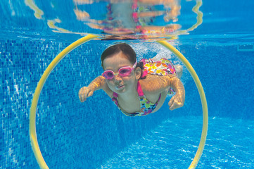 Happy child swims underwater in swimming pool. Kids sport
