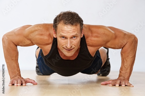 Handsome muscular man doing push-up.