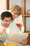 Couple drinking coffee and looking at a newspaper together