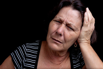 Aged woman suffering from a strong headache