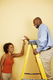 Couple with light bulb on ladder