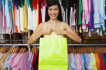 Portrait of woman in clothing store holding bag