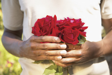 Midsection of man holding roses