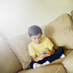 Boy playing hand held video game